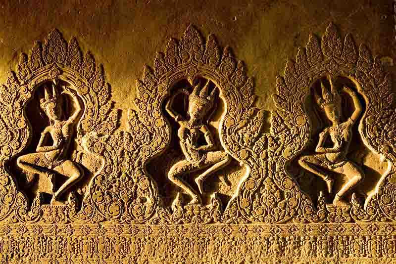Dancing people carved into the stone walls at the temple of Angkor Wat in Cambodia